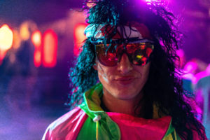 Reminiscent of the quintessential rockstar, this costumed man wearing a wig turns heads.