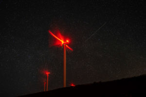 Windmills at night, glowing red light in long exposure and nightsky